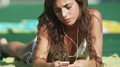 young woman listening to iPod at water park - stock footage