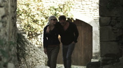 Couple walking down a European street Stock Footage