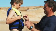 Father putting life jacket on his son Stock Footage