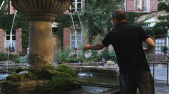 Man filling up water jars from a fountain Stock Footage
