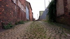 Urban backstreet old stone track and red brick buildings  abandoned spaces Stock Footage