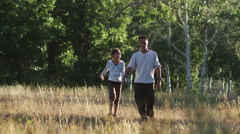 Father and daughter walking through a field Stock Footage