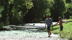 children wading in a river - stock footage