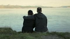 Loving couple by lake with arm around shoulder Stock Footage