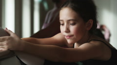 Ballerina stretching and looking at camera Stock Footage