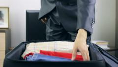 Man unpacking his suitcase  - stock footage