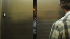 Man playing a joke in an elevator Stock Footage