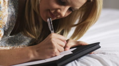 Woman writing a letter on her bed Stock Footage