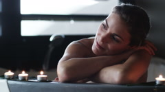 Woman sitting in a bathtub with candles Stock Footage