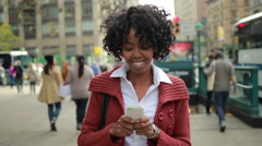 African American black woman in city walking texting smart phone cellphone - stock footage