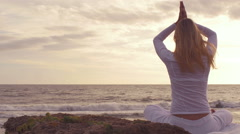 Silhouette young woman practicing yoga on the beach at sunset. Stock Footage