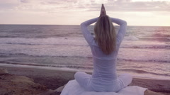 Silhouette young woman practicing yoga on the beach at sunset: meditation - stock footage