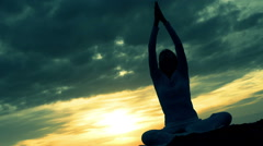 Young woman practicing yoga and meditation on the beach at the sunset Stock Footage