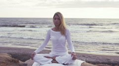 Woman having meditation near the sea: practicing yoga on the beach Stock Footage