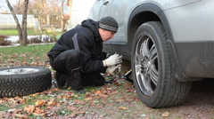 Driver trying to unscrew the wheel bolts for suv snow tyres replacement - stock footage