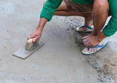 plasterer concrete worker at floor of house construction - stock photo