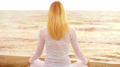 Young woman practicing yoga in sunflares on the beach at sunset - stock footage