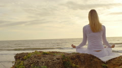 Young woman practicing yoga on the beach at sunset - stock footage
