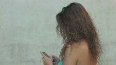 Cute curly blonde girl is using smartphone: mobile phone, communication, chat Stock Footage
