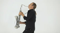 The man in stylish clothing plays a tune on his saxophone Stock Footage