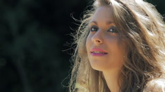 Thoughtful cute girl in a windy day of sun: outdoor, park, thinking, beautiful Stock Footage