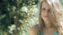 Shy blonde woman smiling: cute young girl in the park Stock Footage