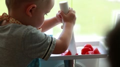 A toddler and pregnant mother juice tomatos Stock Footage