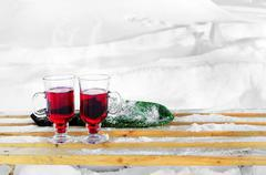 Two glasses of mulled wine and mittens on a snow-covered bench on a snowy bac Stock Photos