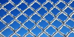 Iron grid covered by ice crystals against blue sky - stock photo
