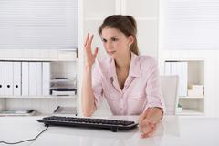 angry and shocked young woman sitting in the office wearing rose blouse. - stock photo