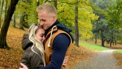 woman cuddles to men - young model happy couple in love - autumn park (nature) - stock footage