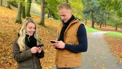 Woman on phone and man on phone (write message) - happy couple smile - park Stock Footage