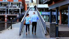 Stock Video Footage of Young couple holding hands walking through footbridge by the canal