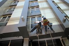Industrial Climbers Washing Facade of a Modern Building Stock Photos