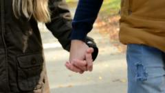 Stock Video Footage of couple walking in park - couple holding hands (closeup) - autumn park(nature)