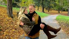 young model couple in love - autumn park- man carries a woman in his arms - stock footage