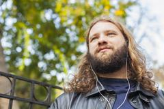 Blond beard young adult hipster man listening music Stock Photos