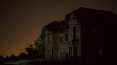 Ruined building night time lapse with plane trails Stock Footage