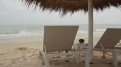 Close-Up White Sun Loungers Under Palm Leaf Parasol Stock Footage