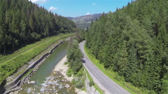 Stock Video Footage of Flight up over   mountain river with wood  and road . Aerial