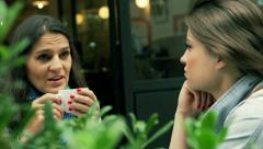 Female friends chatting in the street cafe, steadycam shot Stock Footage