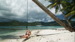 Woman on a swing on the beach Stock Footage
