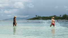 Two women splashing in the ocean Stock Footage