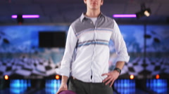 Young man holding a purple bowling ball at a bowling alley Stock Footage