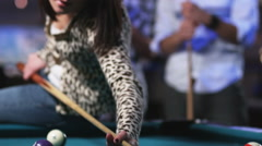 Young men watching a young woman play pool from behind Stock Footage