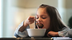 Little girl eating cereal and complaining about drinking a healthy green Stock Footage