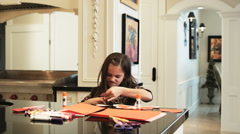 Little girl doing arts and crafts in the kitchen Stock Footage