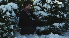 Young couple having a snowball fight in a grove of pine trees Arkistovideo