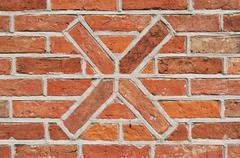 Masonry wall of bricks with a cross as decoration. Stock Photos