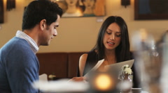 Couple looking at menus in a restaurant Stock Footage